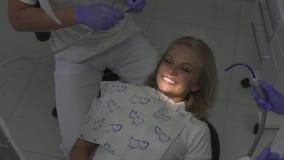 Paziente nel cabitet del dentista Bella ragazza con il sorriso brillante che si siede nella sedia del dentista video d archivio