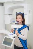 Paziente nella clinica del dentista che fa il raggio di 3d x facendo uso dell'attrezzatura della radiografia Immagini Stock Libere da Diritti