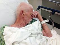 Paziente ricoverato maschio anziano nel letto di ospedale fotografie stock