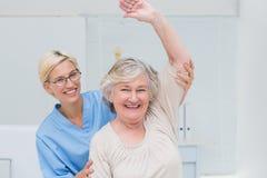 Paziente senior che è assistito dall'infermiere nell'innalzamento del braccio Immagini Stock Libere da Diritti