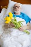 Paziente senior con i fiori del tulipano immagini stock libere da diritti