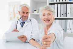 Paziente senior felice che gesturing i pollici su con medico Fotografia Stock