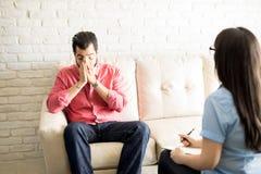 Paziente turbato che dice le sue difficoltà allo psicoterapeuta Fotografia Stock