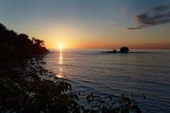 Pazifikküste von Costa Rica in Mittelamerika, Sonnenuntergang mit Palmen, Ozean und Wolken auf dem roten Himmel glättend stockbilder