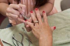 paznokcia ręka robiąca manikiur polerująca czerwień Zdjęcia Royalty Free