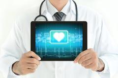 PC ταμπλετών εκμετάλλευσης γιατρών με το σημάδι καρδιών στην οθόνη Στοκ Εικόνες