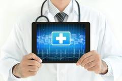 PC ταμπλετών εκμετάλλευσης γιατρών με το σημάδι πρώτων βοηθειών στην οθόνη Στοκ εικόνα με δικαίωμα ελεύθερης χρήσης