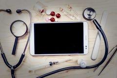 PC ταμπλετών με τα ιατρικά αντικείμενα σε ένα γραφείο Στοκ φωτογραφία με δικαίωμα ελεύθερης χρήσης