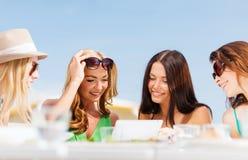 Κορίτσια που εξετάζουν το PC ταμπλετών στον καφέ Στοκ φωτογραφία με δικαίωμα ελεύθερης χρήσης