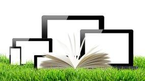 PC ταμπλετών, κινητό τηλέφωνο, υπολογιστής και ανοικτό βιβλίο στην πράσινη χλόη Στοκ εικόνες με δικαίωμα ελεύθερης χρήσης