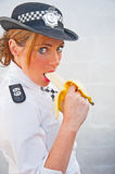 PC 69 eating banana on duty Royalty Free Stock Images