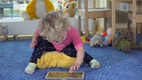PC bonito da tabuleta do uso da menina da criança que senta-se no tapete azul Mãos felizes do aplauso da criança video estoque