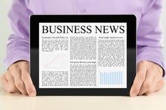 PC da tabuleta com notícia de negócio Fotos de Stock