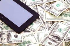 PC de comprimé au-dessus des dollars Photo stock