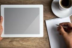 PC de la tableta de Digitaces en el escritorio del negocio con la pantalla en blanco Imagen de archivo
