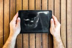 PC de la tableta de la tenencia del hombre en fondo de madera Fotografía de archivo