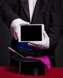 PC de la tableta de la tenencia del mago sobre sus accesorios para el trabajo Fotos de archivo libres de regalías