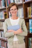 PC de la tableta de la tenencia del profesor en la biblioteca Imagen de archivo libre de regalías