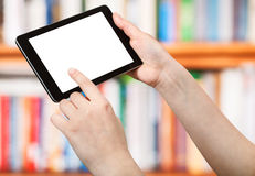 PC de la tableta de tactos del finger en el frente de estantes de librería Fotografía de archivo