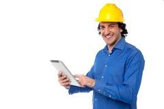 PC de la tableta del funcionamiento del trabajador de construcción Fotografía de archivo libre de regalías