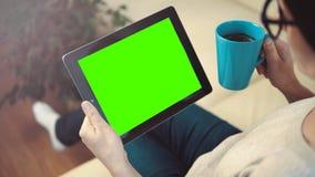 PC de la tableta del uso de la mujer que se sienta en el sofá fotos de archivo libres de regalías