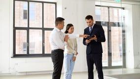 PC de la tableta de la demostración del agente inmobiliario a los clientes en la oficina almacen de video