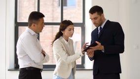 PC de la tableta de la demostración del agente inmobiliario a los clientes en la oficina metrajes