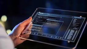 PC de la tableta de la tenencia de la mano con la codificación en la pantalla almacen de video
