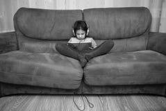 PC de observación de la tableta de la muchacha con los auriculares foto de archivo libre de regalías