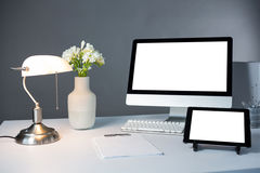 PC de sobremesa, tableta digital y lámpara de mesa con el florero en la tabla Fotos de archivo