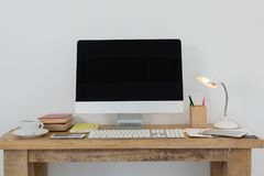 PC de sobremesa y diversos accesorios de la oficina en la tabla Fotos de archivo libres de regalías