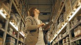 PC de With Tablet de directeur vérifiant des marchandises à l'entrepôt de supermarché Images libres de droits