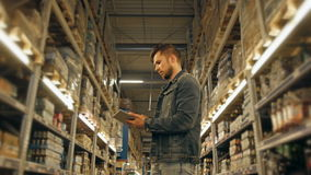PC de With Tablet de directeur vérifiant des marchandises à l'entrepôt de supermarché Image stock