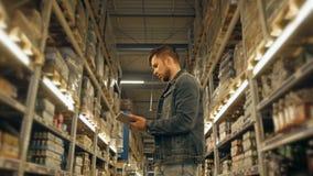 PC de With Tablet de directeur vérifiant des marchandises à l'entrepôt de supermarché Image libre de droits