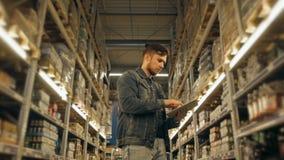 PC de With Tablet do gerente que verifica bens no armazém do supermercado Imagem de Stock Royalty Free