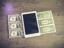 PC de Tablette se trouvant sur des dollars Images stock