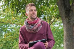 PC de utilização milenar da tabuleta no parque com árvores verdes imagens de stock royalty free