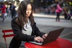 PC del ordenador portátil de la mujer que mecanografía asiática Foto de archivo libre de regalías