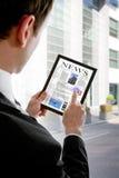 PC del touchpad de la explotación agrícola del hombre de negocios, periódico de la lectura Imagen de archivo libre de regalías