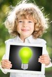PC della compressa della tenuta del bambino con la lampadina royalty illustrazione gratis