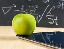 Pc della compressa di Digital e mela verde davanti alla lavagna sulla tavola di legno Fotografia Stock Libera da Diritti