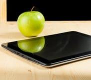Pc della compressa di Digital e mela verde davanti alla lavagna sulla tavola di legno Fotografie Stock Libere da Diritti
