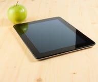Pc della compressa di Digital vicino alla mela verde sulla tavola di legno Fotografia Stock