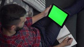PC della compressa di uso dell'uomo con lo schermo ed il taccuino verdi stock footage