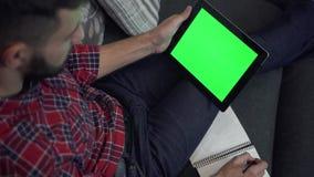 PC della compressa di uso dell'uomo con lo schermo ed il taccuino verdi video d archivio