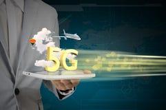 PC della compressa di uso dell'uomo di affari sulla rete di alta velocità 5G Immagini Stock