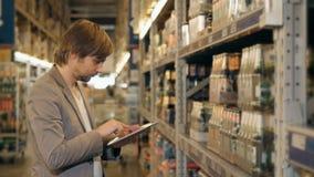 PC di With Tablet del responsabile che controlla le merci al magazzino del supermercato archivi video