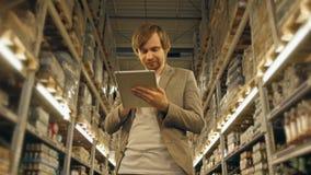 PC di With Tablet del responsabile che controlla le merci al magazzino del supermercato Immagini Stock Libere da Diritti