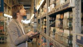PC di With Tablet del responsabile che controlla le merci al magazzino del supermercato Immagini Stock