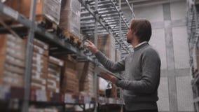 PC di With Tablet del responsabile che controlla le merci al magazzino del supermercato Azione moderne della mobilia archivi video
